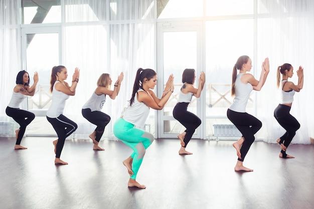 Gruppe der jungen frau, die yoga utkatasana-pose drinnen macht