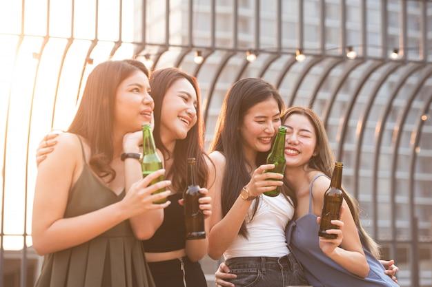 Gruppe der jungen schönen glücklichen asiatischen frauen, die flasche bier halten, plaudern zusammen mit freunden, während tanzparty auf nachtdach im freien mit kopierraum für werbung feiern.