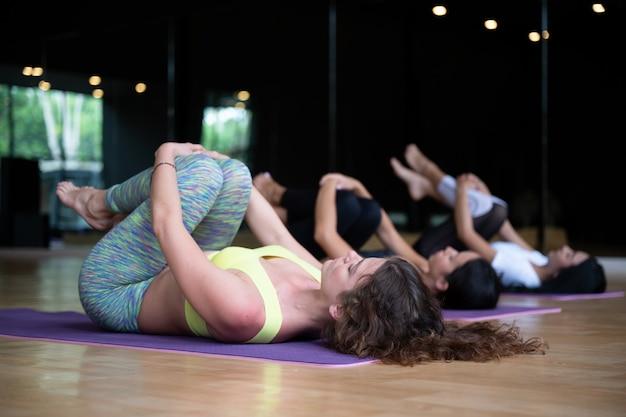 Gruppe der jungen sportlichen frau, übende yogalektion der attraktiven leute an der turnhalle