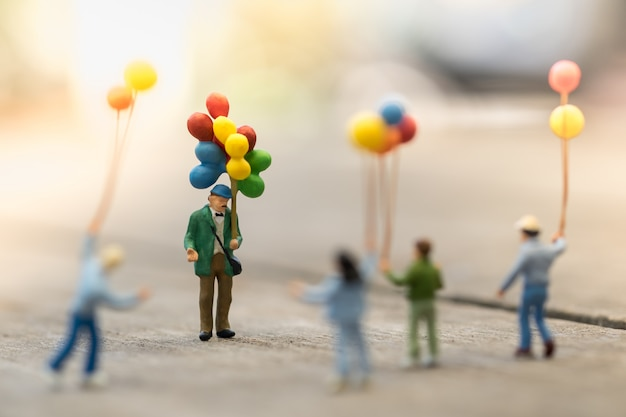 Gruppe der kinderminiaturzahl, die um einen mannballonverkäufer steht und geht
