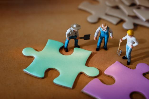 Gruppe der miniaturarbeitskraft arbeitend an puzzle