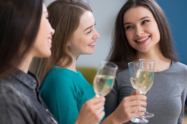 Gruppe der niedlichen jungen frauen, die champagner zusammen haben