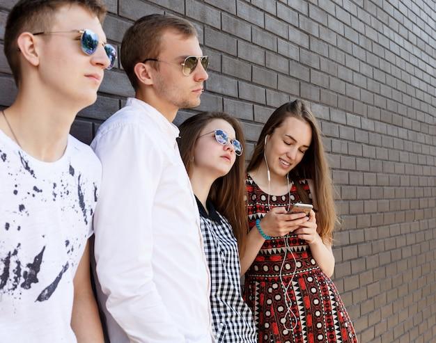 Gruppe der schönen jungen leute, die gegen backsteinmauer stehen