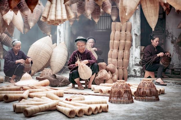Gruppe des alten vietnamesischen weiblichen handwerkers, der die traditionelle bambusfischfalle macht oder am alten traditionellen haus in thu sy-handelsdorf, hung yen, vietnam, traditionelles künstlerkonzept spinnt