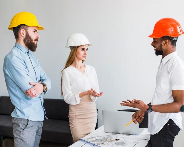 Gruppe des architekten plan im büro besprechend