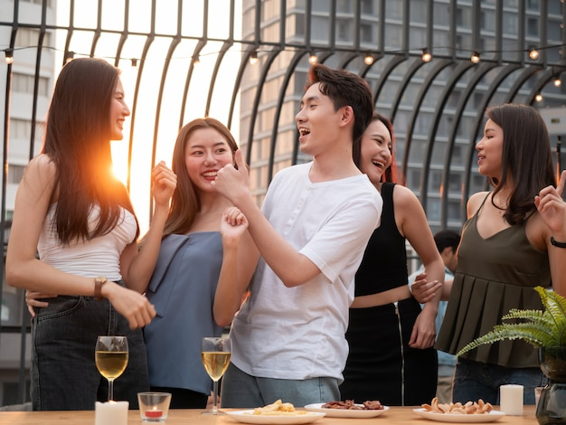 Gruppe des asiatischen freundes, der an der terrassenparty jubelt und trinkt. junge leute genießen und hängen auf dem dach bei sonnenuntergang