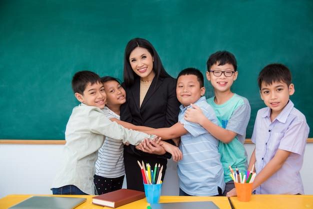 Gruppe des asiatischen studenten ihren lehrer im klassenzimmer umarmend