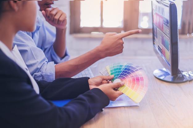 Gruppe des designers arbeitsgrafik auf computer mit farbkarte