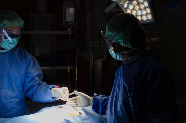 Gruppe des doktors und des behilflichen chirurgen, die raum der in kraft arbeit am krankenhaus durchführen
