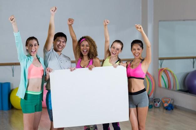 Gruppe des fitness-teams, das leeres plakat und geballte fäuste hält