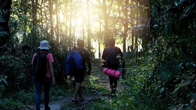 Gruppe des fotografen gehend mit rucksäcken im sonnenuntergang. abenteuer, reisen, tourismus, foto