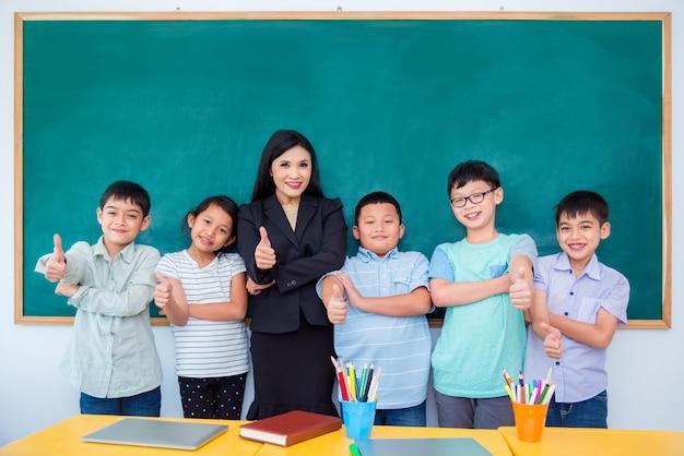 Gruppe des glücklichen asiatischen studenten und des lehrers, die im klassenzimmer steht