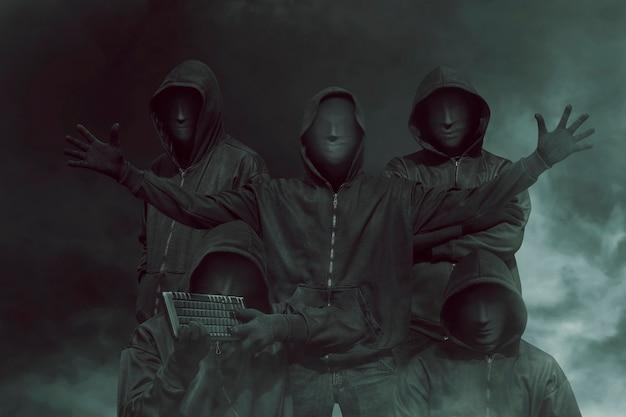 Gruppe des hackers mit maske in den kapuzenpullis