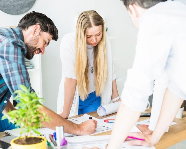 Gruppe des jungen männlichen und weiblichen architekten, der im büro arbeitet