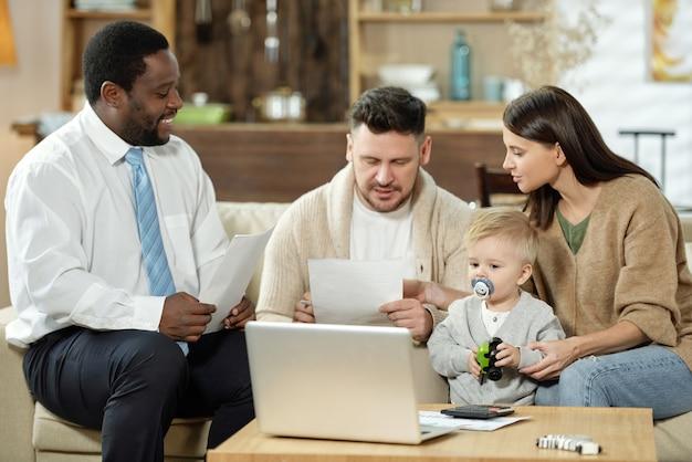 Gruppe des jungen paares mit dem kleinen sohn, der papiere liest, während sie treffen mit immobilienberater zu hause haben