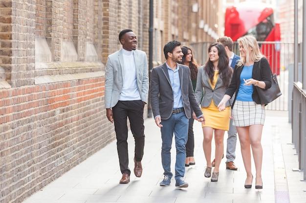 Gruppe des jungen professionellen gehens in der stadt