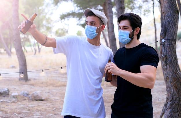 Gruppe des jungen tausendjährigen mannes, der spaß in einem park hat, der auf einer party mit gesichtsmaske, coronavirus, covid-19 trinkt - freunde versammeln sich nach der blockade am aperitif