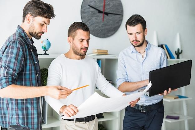 Gruppe des männlichen architekten, der laptop beim betrachten des planes verwendet
