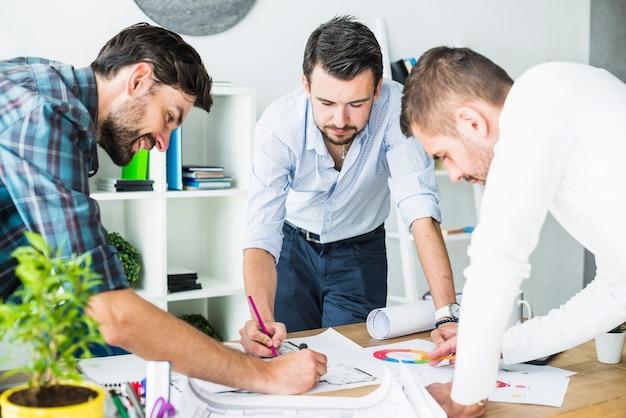 Gruppe des männlichen architekten, der plan über hölzernem schreibtisch plant