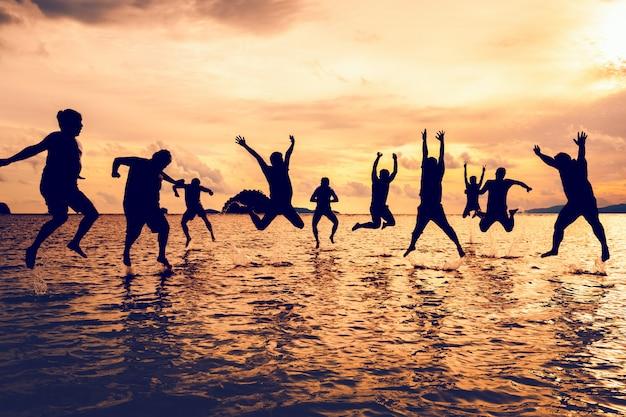 Gruppe des mannes springend auf strand im sonnenuntergang