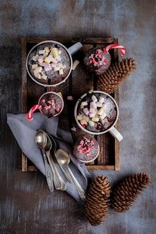 Gruppe des neujahrsschokoladenkuchens gekocht im mikrowellenofen im becher auf weinlesegrauoberflächentextur