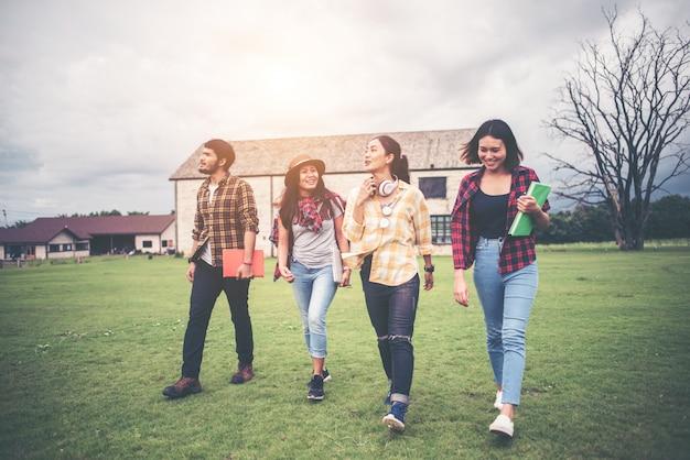 Gruppe des studenten gehend durch den park nach klasse. viel spaß beim reden.