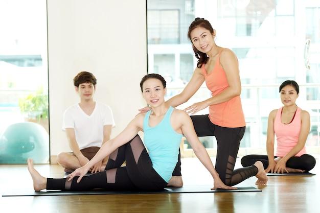 Gruppe des übenden yoga der asiatischen frauen und des mannes, eignung, die flexibilitätshaltung ausdehnt und arbeiten, gesunder lebensstil aus, wellness, wohl, innen, in voller länge, studiohintergrund
