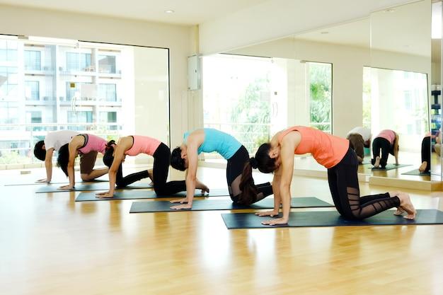 Gruppe des übenden yoga innenstudiohintergrundes der asiatischen leute