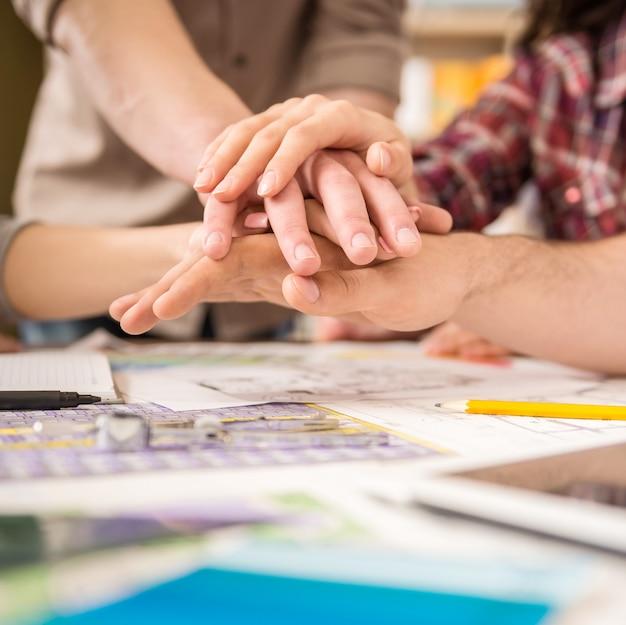 Gruppe designer, die hände zusammenfügen.