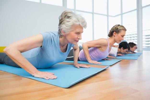 Gruppe, die kobrahaltung in der reihe an der yogaklasse tut