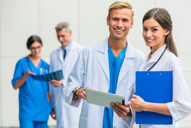 Gruppe doktoren, die auf kamera stehen und aufwerfen.