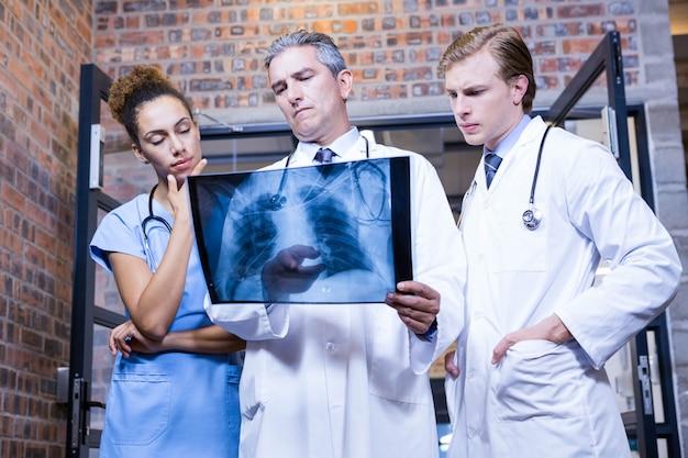 Gruppe doktoren, die axt überprüfen, berichten im krankenhaus