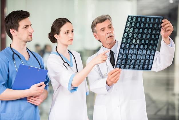 Gruppe doktoren, die röntgenstrahl am offie betrachten.