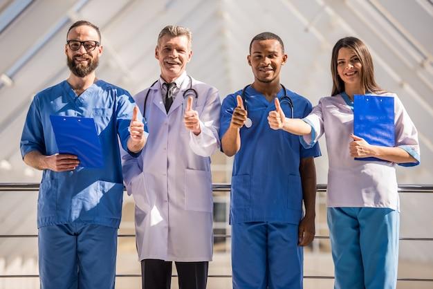 Gruppe doktoren, die sich daumen am krankenhaus zeigen.