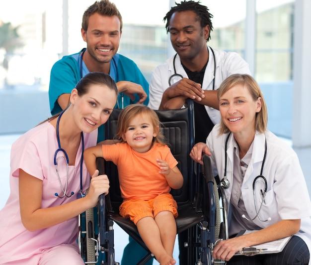Gruppe doktoren mit einem baby in einem rollstuhl