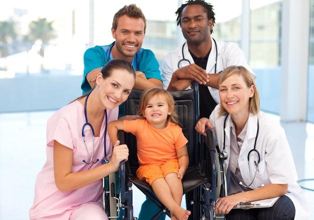 Gruppe doktoren mit einem kleinen mädchen in einem rollstuhl