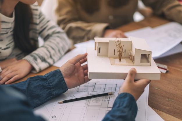 Gruppe eines architekten, der über ein architekturmodell zusammen mit dem zeichenpapier des geschäfts auf tisch im büro arbeitet und diskutiert
