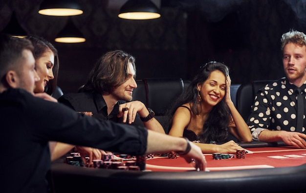 Gruppe elegante junge leute die, die zusammen poker im kasino spielen