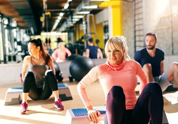 Gruppe engagierter leute, die übungen auf stepper im fitnessstudio machen. im hintergrund ihr spiegelbild.