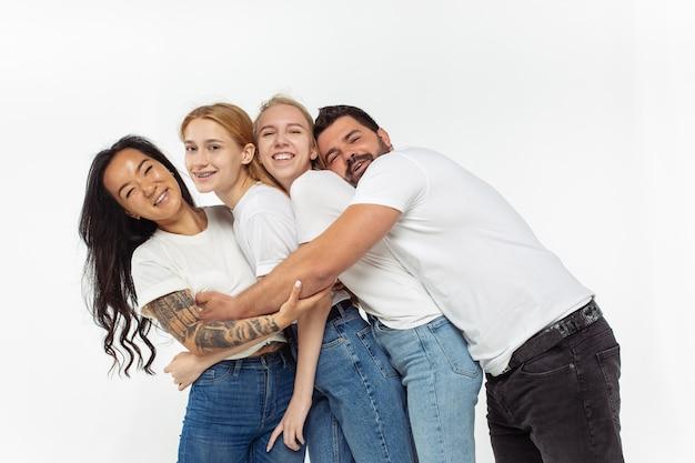 Gruppe entzückender multiethnischer freunde, die spaß isoliert über weißer wand haben