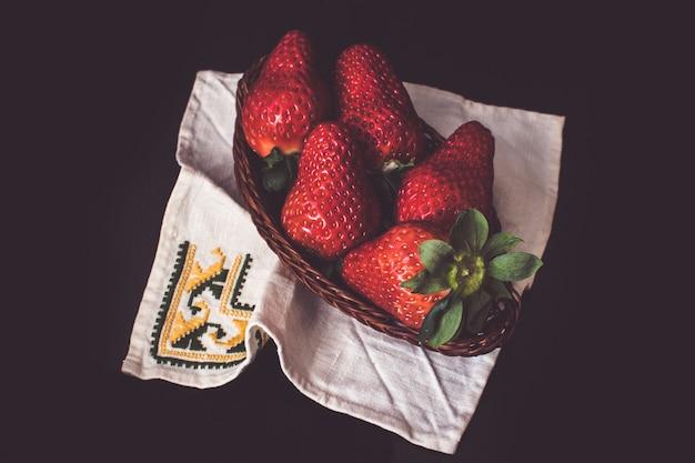 Gruppe erdbeeren in einem korbkasten auf einer serviette. stillleben inspiriert in malerei des xvii. jahrhunderts.