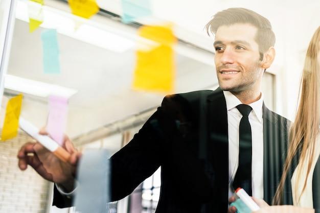 Gruppe erfolgreicher geschäftsteamarbeit brainstorming-meeting mit klebriger papiernotiz an einer glaswand