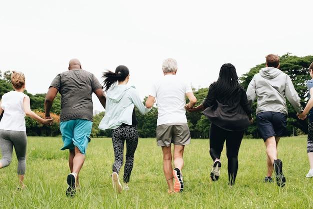 Gruppe erwachsene, die hände im park anhalten