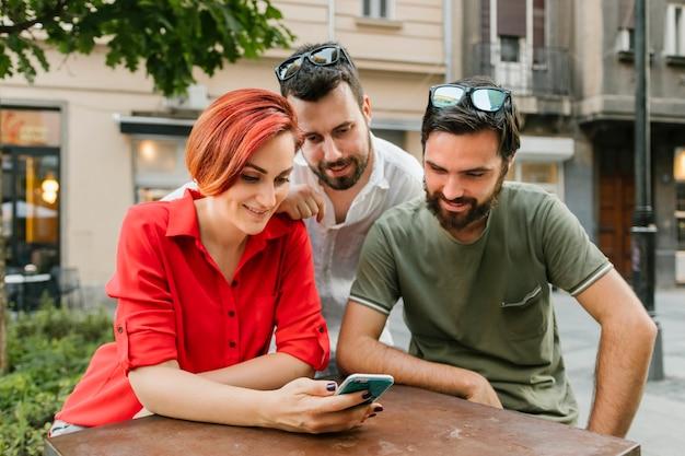 Gruppe erwachsene freunde, die zusammen smartphone auf straße verwenden