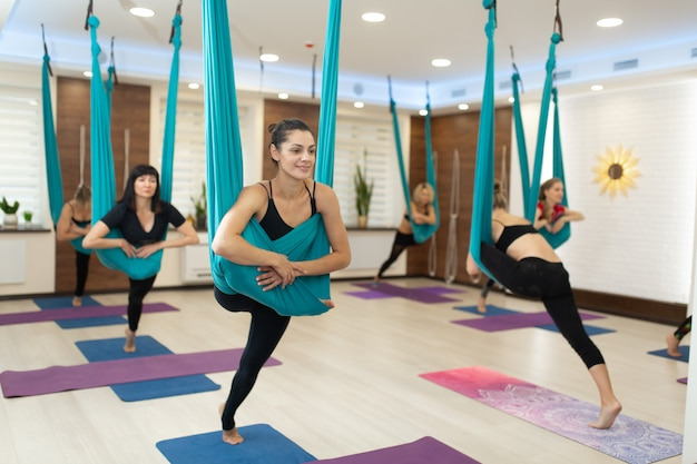 Gruppe frau, die das fliegenyoga ausdehnt übungen in der turnhalle tut. fit und wellness lifestyle.