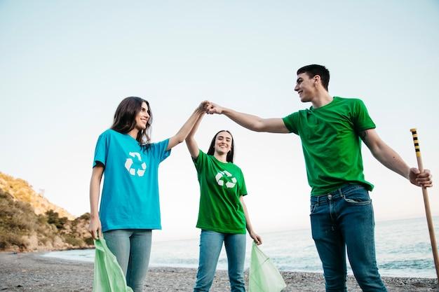 Gruppe freiwillige, die abfall am strand mit teamwork-konzept sammeln