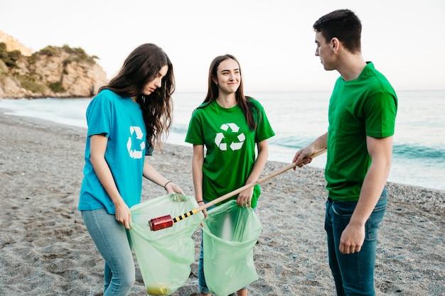 Gruppe freiwilliger, die abfall am strand sammeln