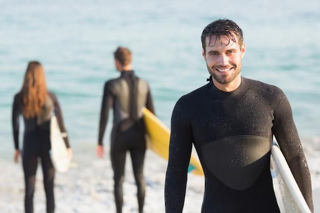 Gruppe freunde auf wetsuits mit einem surfbrett an einem sonnigen tag am strand