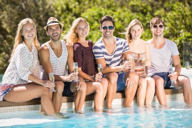 Gruppe freunde, die am poolside mit glas champagner sitzen