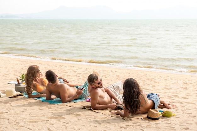 Gruppe freunde, die am strand nehmen ein sonnenbad nehmen